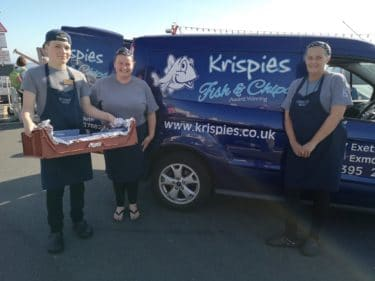 people standing next to a fish and chip van